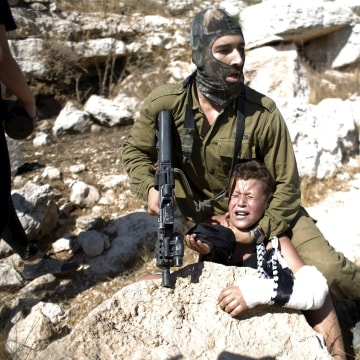 Image: An Israeli soldier detains Mohammed Tamimi