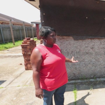 Image: Janice Tambrella outside her damaged and unfinished home.