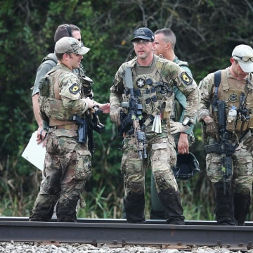 Image: Police officers search an area for suspects involved in shooting an officer