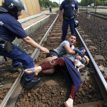 Image: Hungarian police officers stand by migrants at the railway station in the town of Bicske