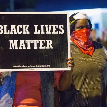 Image: A demonstrator holds a Black Lives Matter Sign