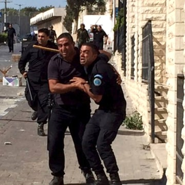 Image: A Palestinian policeman reacts next to fellow officers