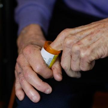 Image: A man reaches into a medicine bottle
