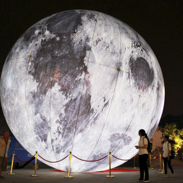 """Image: Visitors look at a """"moon"""" balloon on display ahead of the Mid-Autumn Festival at a square in Nanjing"""