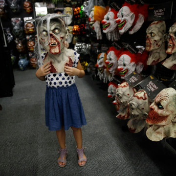 Image: Girl wears zombie mask at a Halloween store