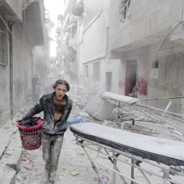 Image: A boy carries his belongings after alleged barrel bombing in Aleppo