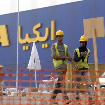 Image: Moroccan workers walk past the construction site of the country's first Ikea store near Casablanca, Morocco,