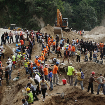 Image: Rescue team members and volunteers remove dirt with buckets from the site of a mudslide in Santa Catarina Pinula