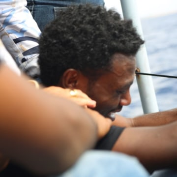 Image: An Eritrean migrant who survived a shipwreck off the coast of the Italian island of Lampedusa is overcome with emotion