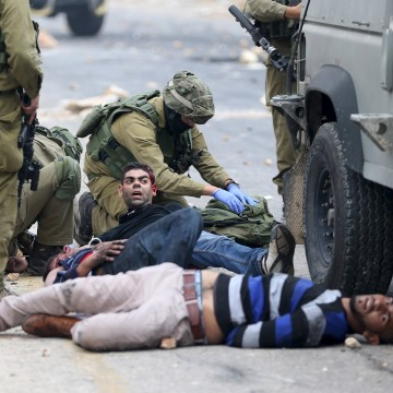 Image: Israeli soldiers detain wounded protesters in West Bank