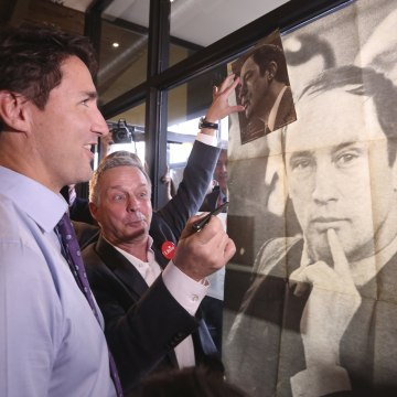Image: Justin Trudeau looks at poster of his late father
