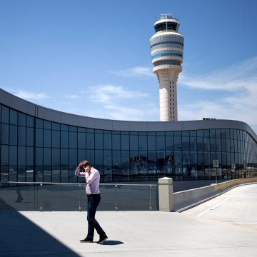 Image: A passenger walks while on the phone outside the international terminal at Hartsfield-Jackson airport