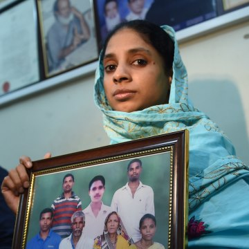 Image: Geeta holds a photograph possibly of her family on Oct. 15