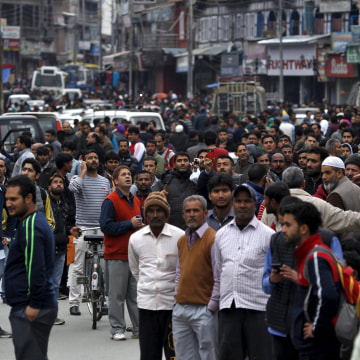 Image: People stand on a road after vacating buildings