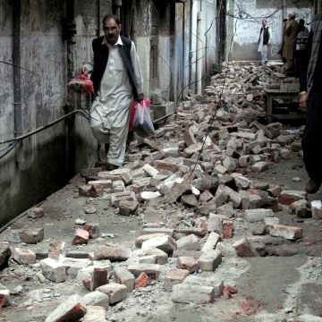 Image: A man with his belongings walks past the rubble of a house after it was damaged by an earthquake in Mingora