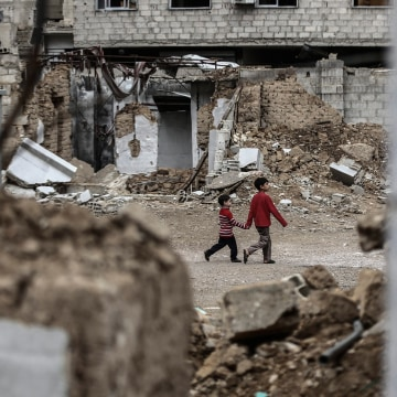 Image: Two young Syrian boys hold hands as they walk past destroyed houses