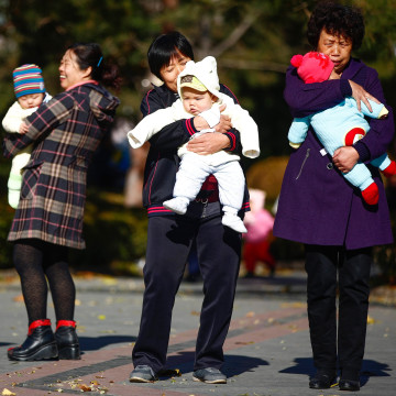 Image: Parents and babies gather at a park in Beijing