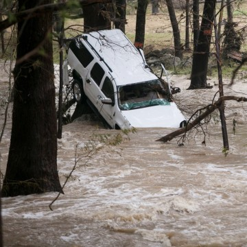 Image: A car washed up against a tree in Cyprus Creek, a tributary of the Blanco River, in Wimberley