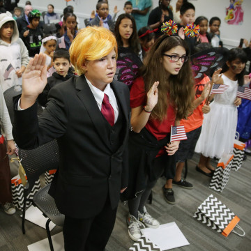 Image: A teenager dressed as Donald Trump takes the Oath of Allegiance