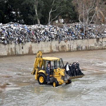 """Image: """"You Stink"""" activists ride on the front of a loader during a campaign to remove piled garbage on the bank of Beirut river"""