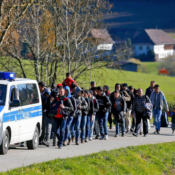 Image: Migrants are escorted by German police to a registration centre, after crossing the Austrian-German border in Wegscheid near Passau
