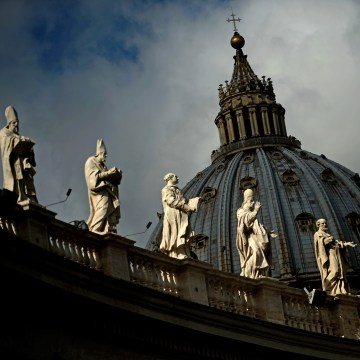 Image: Statues and the dome of St. Peter's basilica at the Vatican in Rome