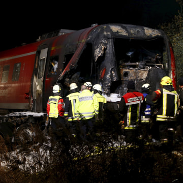 Image: Firefighters look for the train driver
