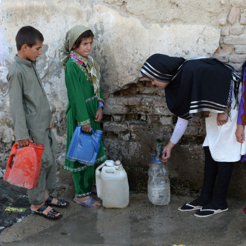 Image: Aziza Rahimzada, (second-from-right), collects water along with other children who live in her encampment in Kabul.
