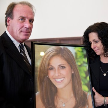 Image: Jim Burk, left, and Viviane Guerschon, right, hold a portrait of their daughter Lauren Burk