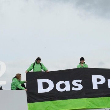"""Image: Greenpeace activists demonstrate as they stand on top of Volkswagen's """"Sandkamp"""" gate in Wolfsburg"""