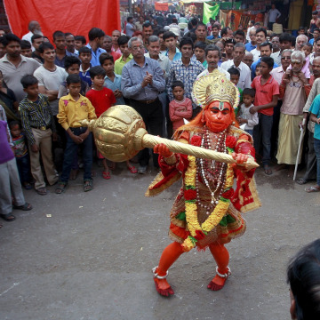 Image: A man dressed as Hindu monkey god Hanuman performs on a street during Hanuman Jayanti Festival in Allahabad