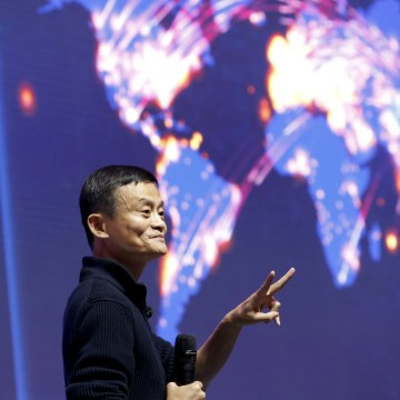 Image: Alibaba founder and chairman Jack Ma gestures in front of a screen
