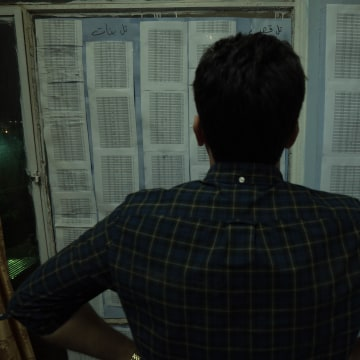 "Image: Yazidi activist ""Iskander"" looks at his list of more than 6,000 Yazidis captured by ISIS"