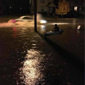 Image: A man pictured kayaking along Church Street in Iowa City.