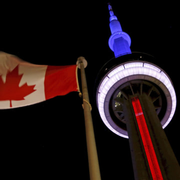 Image: Toronto's landmark CN Tower is lit blue, white and red in the colors of the French flag following Paris attacks
