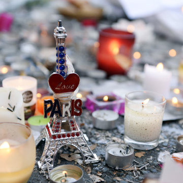 Image: Candles and a small statue of the Eiffel tower at a memorial