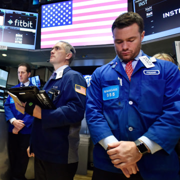 Image: Traders pause for a moment of silence for Paris attack victims at the New York Stock Exchange.
