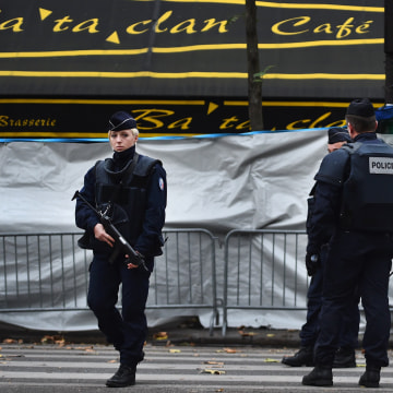 Image: French police officers stand guard in front of the main entrance of Bataclan