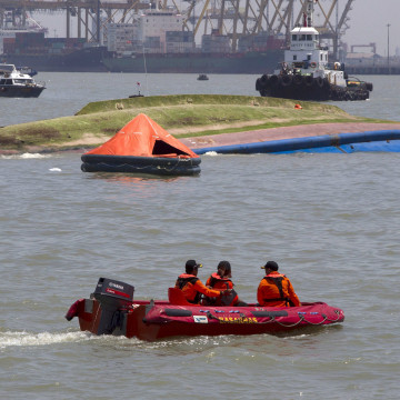 Image: A search and rescue team patrols near the ferry KM Wihan Sejahtera after it capsized in the port of Tanjung Perak, Surabaya, East Java