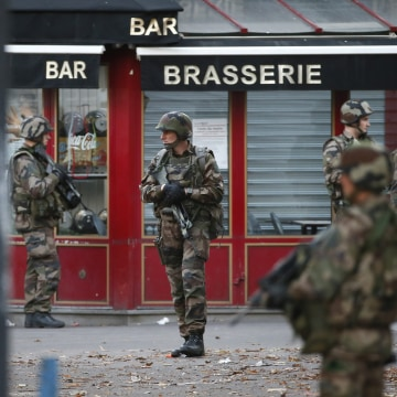 Image: French military members stand guard near the site of a raid