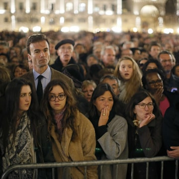 Image: People gather outside Notre Dame Cathedral where a mass is held following a series of deadly attacks in Paris