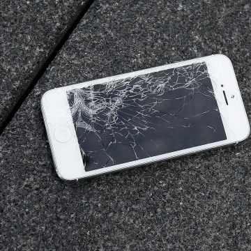 Image: A smartphone with a cracked screen lays on the ground