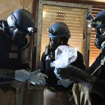 Image: A U.N. chemical weapons expert holds a plastic bag containing samples from one of the sites of an alleged chemical weapons attack in Ain Tarma
