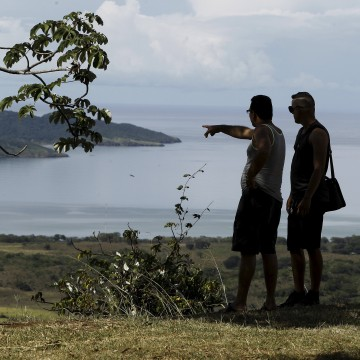 Image: Two Cuban migrants look towards the sea in the town of La Cruz near the border between Costa Rica and Nicaragua