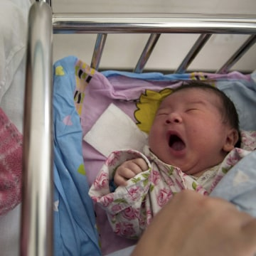 Image: Li Yan looks at her newborn baby at a hospital in Hefei