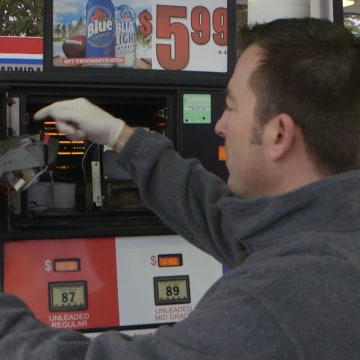 Photo: Craig VanBuren, director of the Consumer Protection Section at Michigan's Department of Agriculture, shows how the skimmer devices are placed inside a gas pump.