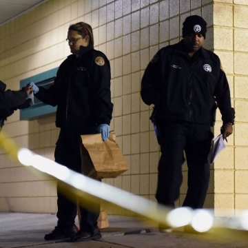 Image: Police gather evidence after a shooting at a playground