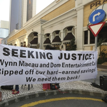 Image: A protester adjusts a banner during a demonstration by investors of Dore Holding's VIP room, outside Wynn Macau in Macau