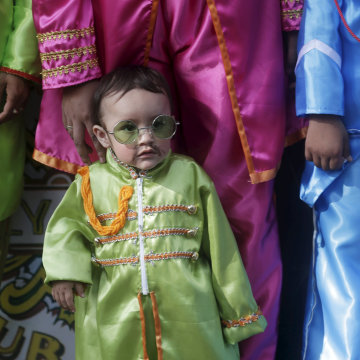 Image: A child dressed as The Beatles takes part in an attempt to set a Guinness World Record for the largest number of people dressed as the British band The Beatles at a park in Mexico City