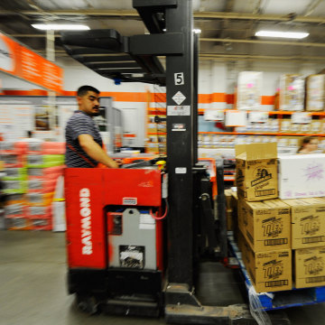 Images: A man drives a forklift full of supplies